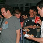 Image of several people drinking coke and eating hot dogs in the evening.