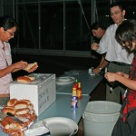 A person preparing hotdogs and serving them to several people.