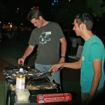Two people cooking hotdogs on a bbq.