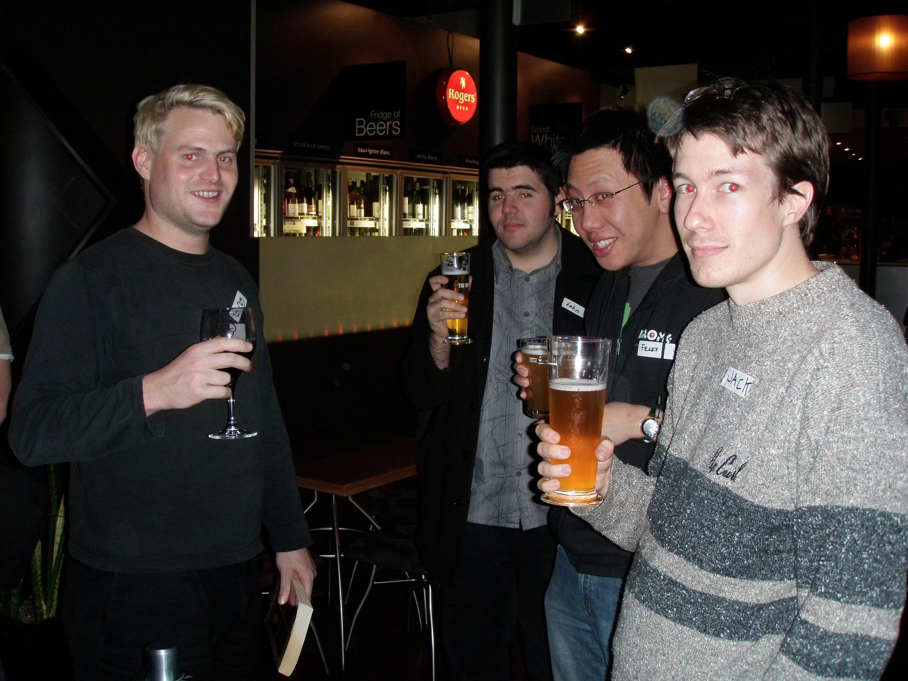 Four people holding drinks and looking at the camera.