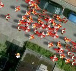 URL Link goes to the Binary Space website. Screenshot is from their game 'Zombie Outbreak Simulator'. A shot of a street from directly above, looking down. There are the roofs of houses either side, green of front gardens, and two cars parked on the street. Along the round are hundreds of bloodied zombies.