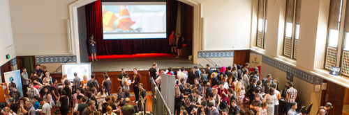 Banner: The Perth Town Hall, filled with people crowding around various game screens and tables. A screen hangs above the stage, showing the image of local game 'Paradigm'
