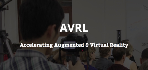 "Image text reads: ""AVRL. Accelerating Augmented & Virtual Reality"". Darkened background image depicts a group of people from behind, looking towards a whiteboard. The man in the foreground is holding up a camera to record the presentation they are watching."