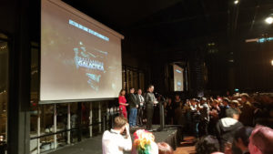 A photograph from the AGDA event,; Paul Turbett and the Black Lab Games team receives their award, as the screen behind them displays the game title .