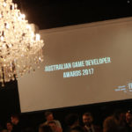 "A projector screen sits above a crowd of people, framed to the left by a chandelier. On the screen, text is displayed which reads ""Australian Game Developer Awards 2017"","