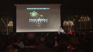A photograph from the AGDA event,; Jacob Janerka receives his award, as the screen behind him displays the game title Paradigm and its main character.
