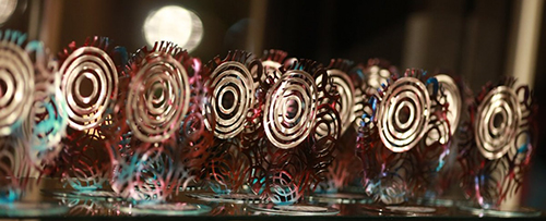 A series of AGDA award trophies laid out horizontally across a table, Each trophy is made up of waves of metal, with four golden concentric circles at the center of each one.