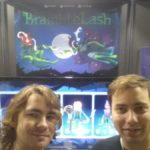 The team members from Bytesprite, Liam and Sam, pose for a photograph in front of the BrambleLash booth. In the background the game's character selection screen is being displayed on a monitor, and the promotional poster hangs on the back wall.