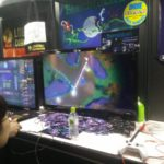"A photograph of the BrambleLash booth during the 2017 Tokyo Games Show. On the screen two players are connected with a glowing vine and are about to run it across an enemy blob. A pile of promotional cards are piled in front of the monitor, and a sticker sits at the top right corner of the booth stating ""Indie Prize Nominee: 4Gamer.net"""