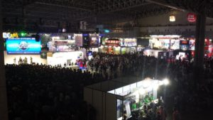 A photograph of the showroom floor at the Tokyo Games Show in 2017. Huge crowds of people fill the space and surround the games booths.