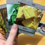 A hand hold up a selection of game cards, with the Dairy/Butter ingredient card at the top. On the table a collection of other food-based cards are laid out.