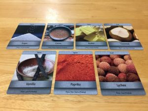 The final selection of game ingredient cards is laid out on the table. They are Sugar, Cocoa, Butter, Coconut, Vanilla, Paprika, and Lychee.