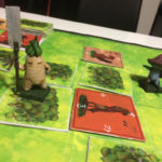 Photograph: A tabletop game with a board depicting grass and trees, and two large models of game characters sitting upon it. One, a radish with short arms and legs holds a long blunted spear weapon, the other, a smaller Mushroom-like person pointing an also brandishing a similar weapon.