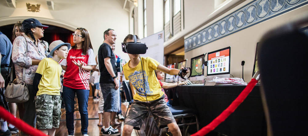 A young boy in the foreground wears a virtual reality headset and is punching his arm forwards. In the background is a crowd of people playing computer games at the Perth Town Hall.