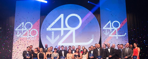 A crowd of award-winners stand on stage, in front of 40 Under 40 signage.