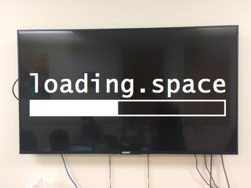 "A television mounted to the wall, with the text ""loading.space"" with an image of a progress bar filling up beneath it."