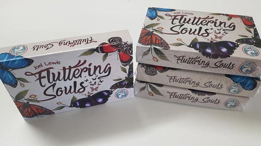 Boxes of the butterfly-themed boardgame Fluttering Souls, by Joel Lewis. Three are stacked on the right, one is flipped on it's side on the left.