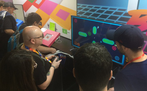 On the left, a man sits facing a screen with a game controller in his hands. Two other men stand watching the screen, their backs facing the camera. On the monitor is the game Teleblast; for green oblong obstructions are present, with triangular player characters present.