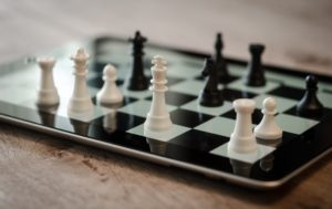 Header Image of Chess set atop a tablet screen with checkerboard effect.