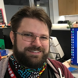 Photograph of Matt Dyet, LMG Chairperson as of 2019. A caucasian man smiling with short brown hair, beard and moustache. He has thin metal glasses, and wears a bandanna around his neck.