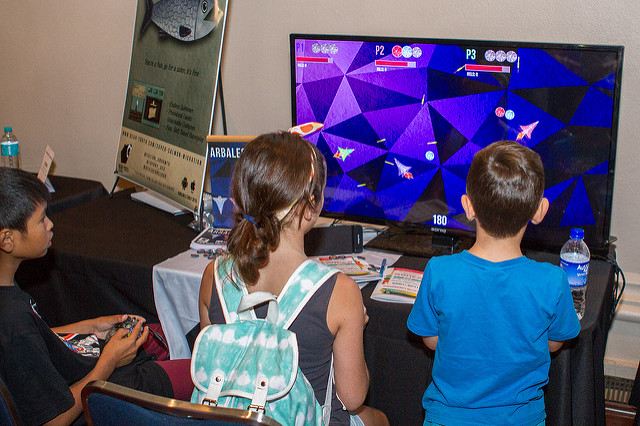 3 kids sit in front of a large screen, playing a stylised spaceship game together.