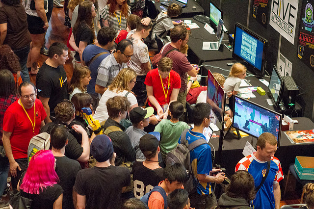 A group of people standing shoulder-to-shoulder, playing games by a local studio