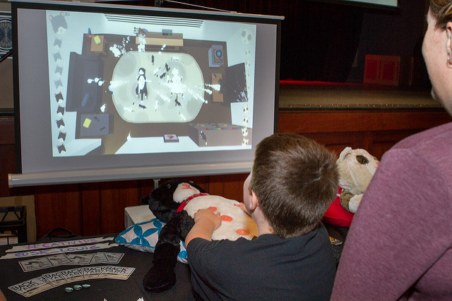 A child plays a game using a large plushi cat as the controller