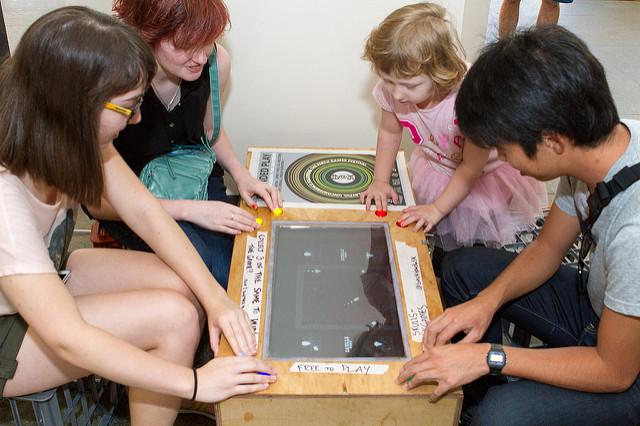 3 young adults and a small child sit around a table that has a digital game built into it's surface.