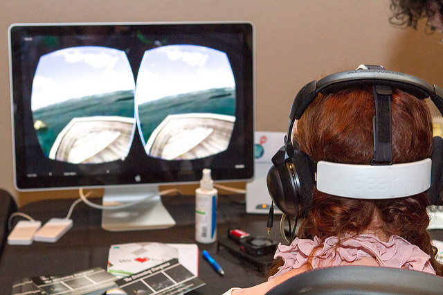 A woman wears a virtual reality headset, and a view from within the game can be seen on the screen in front of her.
