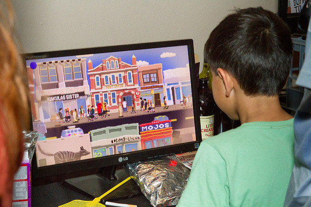 A young boy plays a game that features a cartoony street that looks a lot like Fremantle