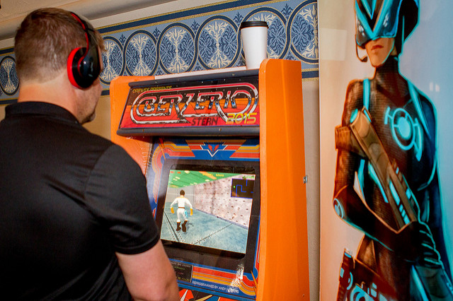 A man wearing headphones plays games on a custom-built arcade machine.