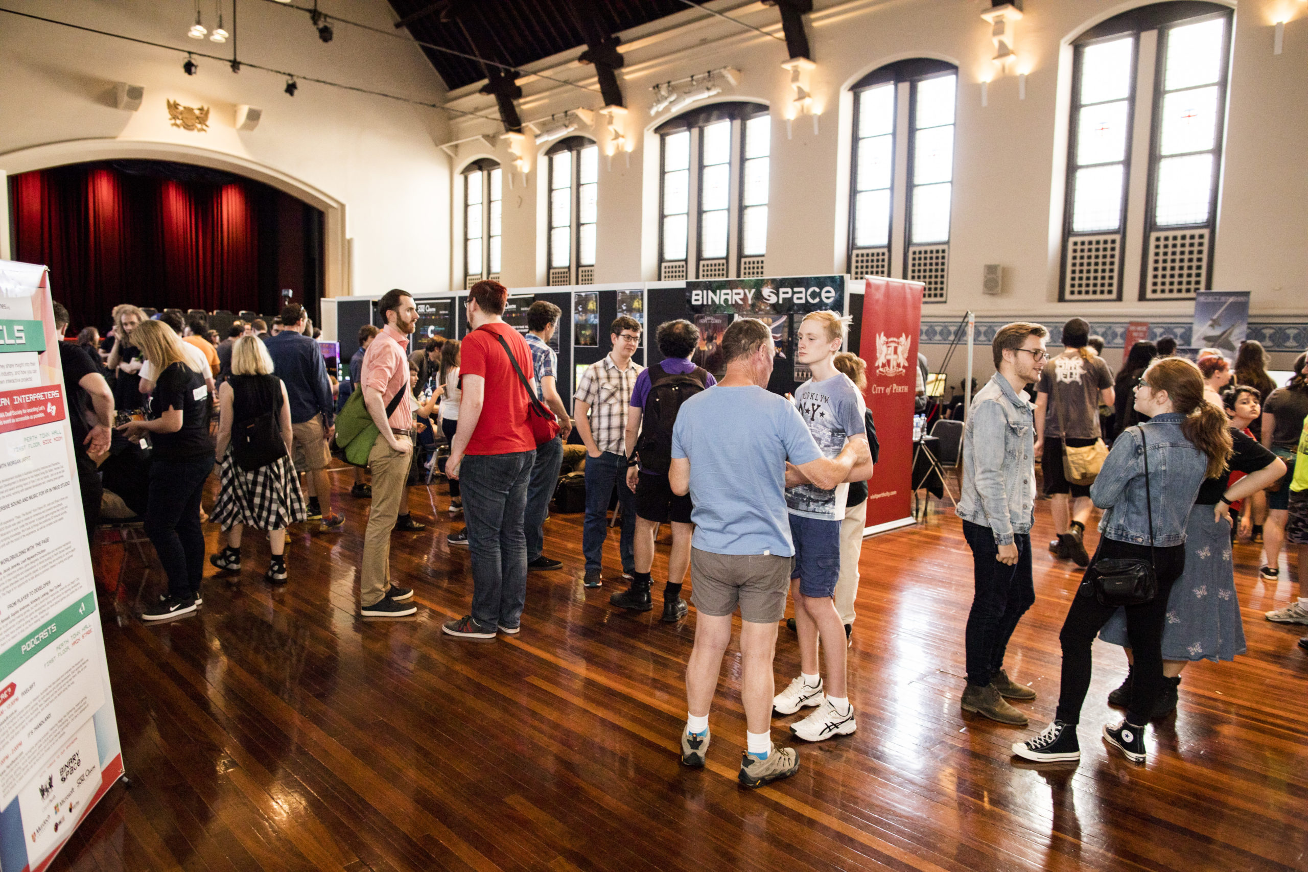 Photo of people standing around game stalls, at a previous Perth Games Festival event in Perth Town Hall